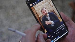 Une personne regarde sur son téléphone portable une des vidéos publiées sur Facebook par l'homme d'affaires syrien Rami Makhlouf, le 11 mai 2020 à Damas