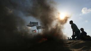 Des manifestants palestiniens mettent le feu à des drapeaux israéliens, le 10 avril à la frontière entre Gaza et Israël.