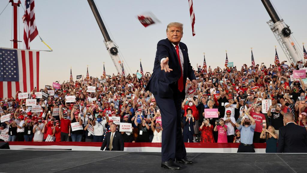 El presidente de los Estados Unidos, Donald Trump, arroja mascarillas a la multitud mientras sube al escenario para un mitin de campaña en el Aeropuerto Internacional Orlando Sanford en Sanford, Florida, EE. UU., 12 de octubre 2020.