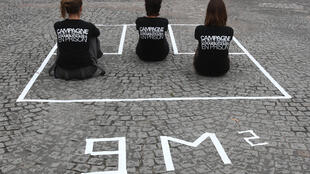 "Three members of the collective ""Trop c'est trop"" sit in a nine-square-metre area drawn on the ground, reconstituting in actual size a prison cell, on October 2, 2007 on the Place de la Concorde in Paris, France to denounce prison overcrowding."
