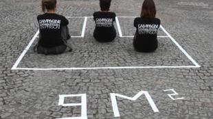 """Trois membres du collectif """"Trop c'est trop"""" sont assises dans un carré de 9 m2 dessiné sur le sol et reconstituant en taille réelle une cellule de prison, le 2 octobre 2007, place de la Concorde à Paris, pour dénoncer la surpopulation carcérale et demander l'application d'un numerus clausus en prison."""