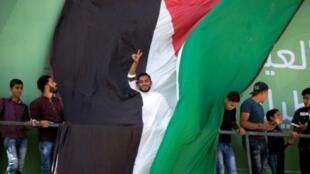 رجل يرفع شارة النصر وراء علم فلسطيني عملاق وسط تجمع لفلسطينيين عند معبر بيت حانون خلال انتظار وصول رئيس الوزراء الفلسطيني رامي الحمد الله مع الوفد المرافق إلى غزة 2 تشرين الأول/أكتوبر 2017