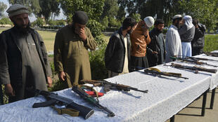Former Afghan Taliban fighters stand next to weapons before handing them over as part of a government peace and reconciliation process at a ceremony in Jalalabad on March 1, 2020.