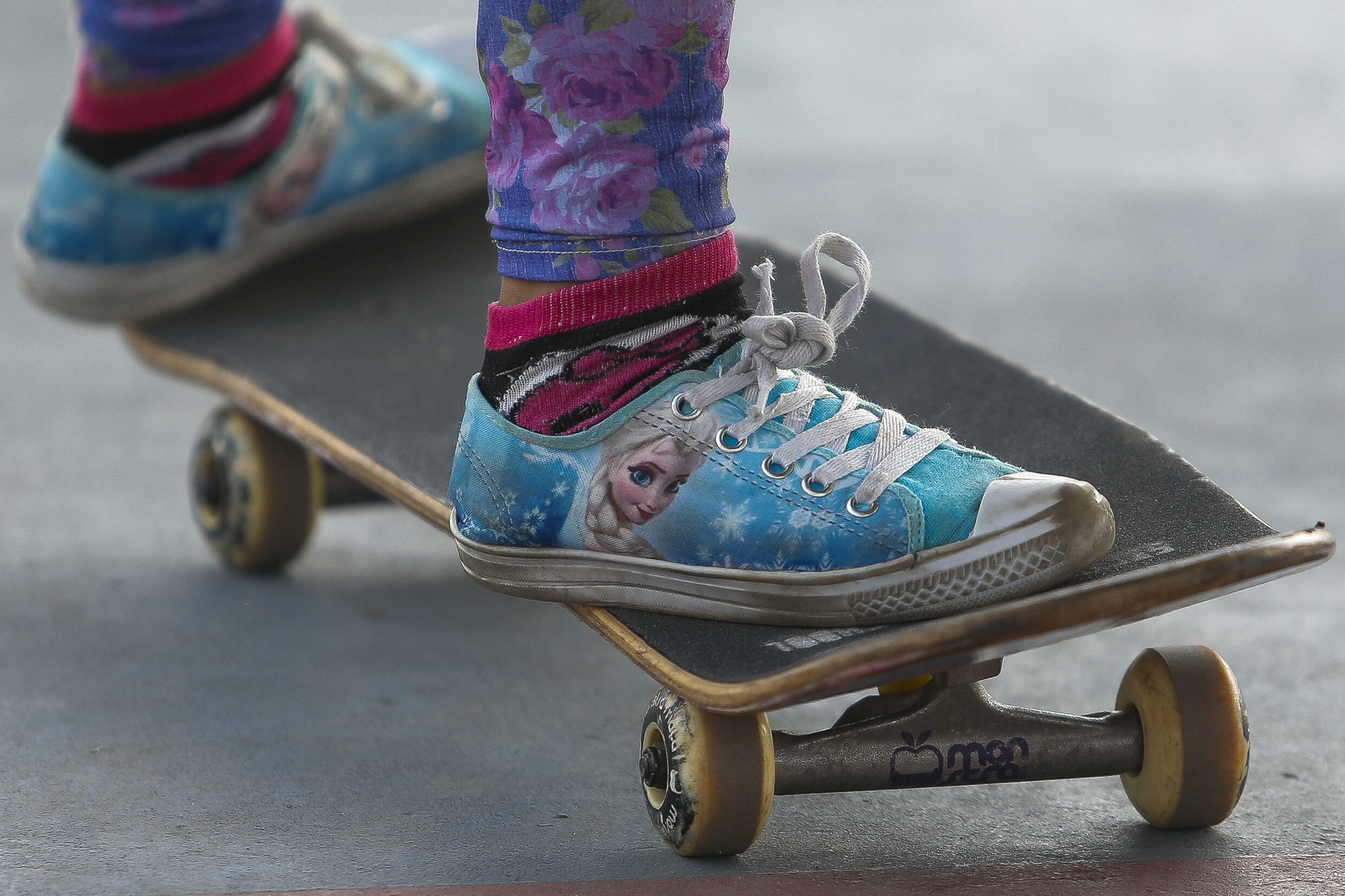 """This young girl is wearing sneakers from the Disney movie """"Frozen"""" as she skateboards"""