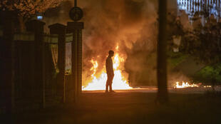 A person stands in front of the flames in Newtownabbey, Befast on April 3, during a week of rioting