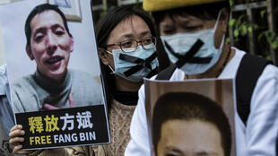 Une militante pro-démocratie tient une pancarte où l'on voit le journaliste citoyen disparu Fang Bin, dans une manifestation à Hong Kong, le 19 février 2020.