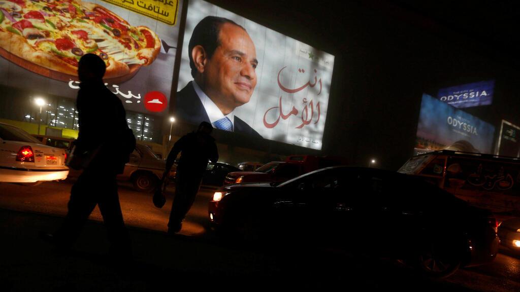 La gente camina cerca de una cartelera que muestra una imagen del presidente egipcio Abdel Fattah Al-Sisi durante las elecciones presidenciales en El Cairo, Egipto, el 28 de marzo de 2018.
