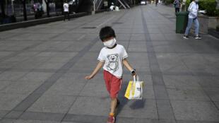 طفل يضع كمامة ويحمل كيساً للتسوّق في أحد شوارع بكين في 23 أيار/مايو 2020