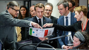 French President Emmanuel Macron, French Health Minister Olivier Véran (2nd from right) and others listen to professor Pierre Carli (at left), the director of Necker hospital's SAMU-SMUR emergency services, during a visit to the hospital on March 10, 2020.