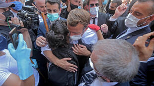A Lebanese youth hugs Macron during a visit to the Beirut's badly-hit Gemmayzeh neighborhood