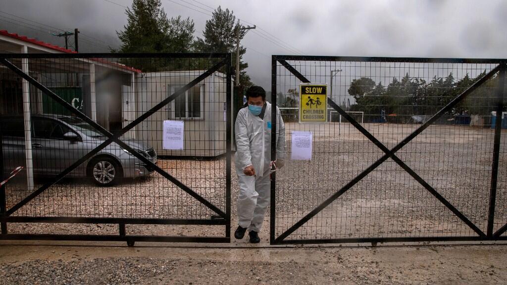 Un hombre vestido con un traje protector y una máscara facial sale del campamento de migrantes de Malakasa después de que las autoridades encontraron un caso de coronavirus y lo pusieron en cuarentena. En Malakassa, Grecia. El 5 de abril de 2020