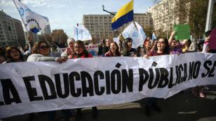 Profesoras despliegan un cartel durante una protesta de profesores y estudiantes, en Santiago de Chile, Chile, el 3 de junio de 2019.