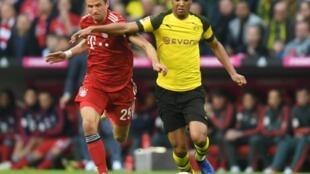 Le défenseur de Dortmund Abdou Diallo (d) à la lutte avec l'attaquant du Bayern Thomas Müller en Bundesliga, le 6 avril 2019 Munich
