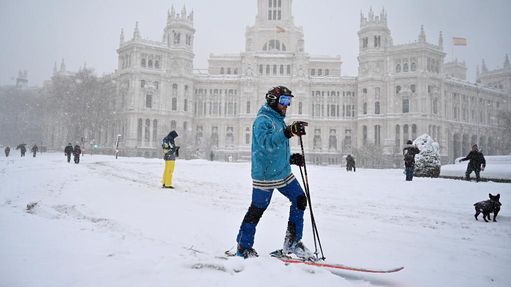 Un madrileño se desplaza en el centro de la capital de España con esquíes, en una imagen insólita.