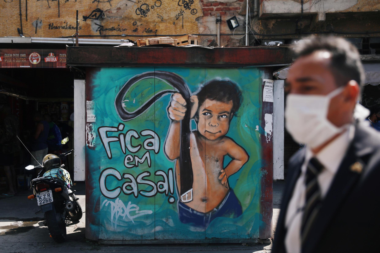 """Un homme portant un masque passe devant un graffiti """"Restez chez vous"""" à Rio de Janeiro, le 2 septembre 2020."""
