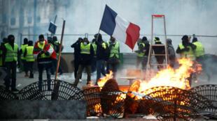 """Los manifestantes de los Chalecos Amarillos están detrás de una barricada mientras se enfrentan a la policía durante los enfrentamientos como parte de un día nacional de protesta por el movimiento """"Chalecos Amarillos"""" en París, Francia, el 8 de diciembre de 2018."""