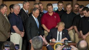 Donald Trump signe le décret abrogeant une série de réglementations édictées du temps de Barack Obama, le 28 mars 2017.