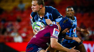 Burger Odendaal (L) of the Northern Bulls is tackled during a Super Rugby loss to the Queensland Reds in Brisbane this season