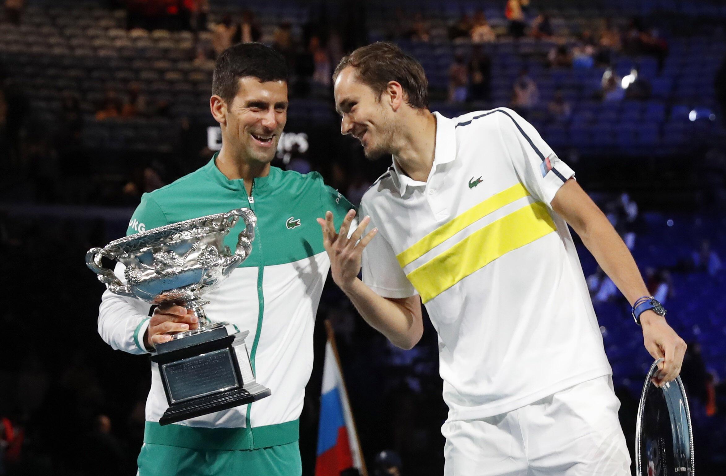El ganador del torneo, el serbio Novak Djokovic, y el subcampeón, el ruso Daniil Medvedev, sostienen sus trofeos tras su partido final.