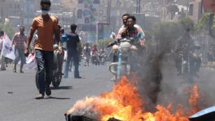 Des pneus brûlés lors d'une manifestation contre la milice des Houthis à Taez, le 25 mars.