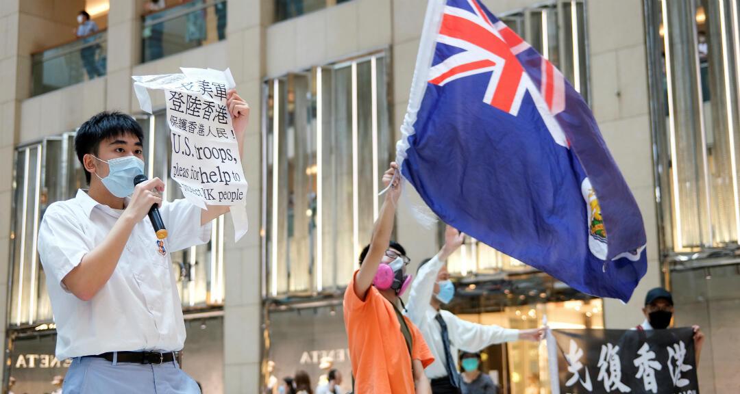 Un manifestante prodemocrático ondea una bandera colonial británica de Hong Kong mientras su compañero sostiene un cartel durante una protesta contra la legislación de seguridad nacional en Hong Kong, el 1 de junio de 2020.