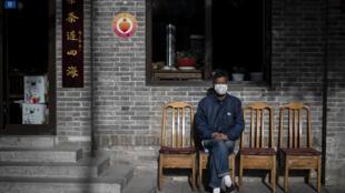رجل يضع كمامة للوقاية من فيروس كورونا المستجد في أحد شوارع العاصمة الصينية بكين في 10 أيار/مايو 2020