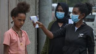 Ethiopian health ministry take a girl's temperature during door-to-door screening in Addis Ababa