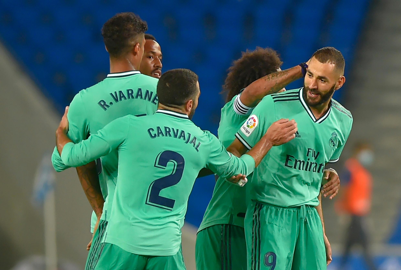 L'attaquant français du Real Madrid, Karim Benzema (d), félicité par ses coéquipiers après son but lors du match de Liga face à la Real Sociedad, à San Sebastian, le 21 juin 2020
