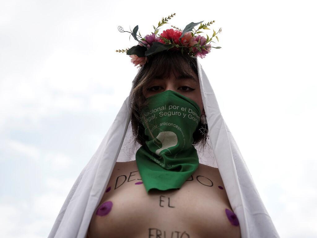 Una mujer usa un pañuelo verde, que simboliza el movimiento por el derecho al aborto, mientras posa para una foto durante una marcha para conmemorar el Día Internacional de la Mujer en Bogotá, Colombia, 8 de marzo de 2020.
