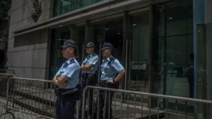 Policías montan guardia en la entrada del cuartel Wanchai, donde se observan algunas de las barricadas puestas por manifestantes, en Hong Kong. 22 de junio de 2019.