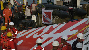 Indonesian crew to hoist recovered wreckage of AirAsia flight QZ8501 at port in Kumai on January 11, 2015. One of two black boxes has been retrieved from under one of the wings.
