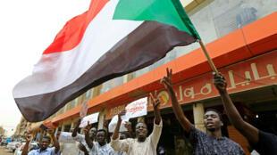 Miembros de la alianza sudanesa de oposición y grupos de protesta ondean su bandera nacional frente a un bloque de oficinas en Jartum, Sudán, el 28 de mayo de 2019.