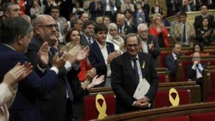 Quim Torra, el candidato propuesto por el exlíder Carles Puigdemont para encabezar el gobierno regional catalán, es aplaudido por sus compañeros diputados del partido, después de pronunciar su discurso durante un debate de investidura en el parlamento en Barcelona, España, el 12 de mayo de 2018.