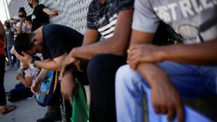 Migrantes del programa 'Permanecer en México' hacen fila fuera de las instalaciones del Instituto Nacional de Migración (INM) para renovar su permiso de permanencia legal en México, en espera de su audiencia de migración en Estados Unidos. Imagen en Ciudad Juárez, México, el 8 de julio de 2020.
