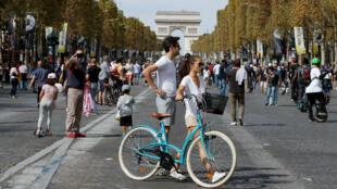 Des cyclistes profitent de la Journée sans voiture sur les Champs Elysées à Paris, le 16 septembre 2018.