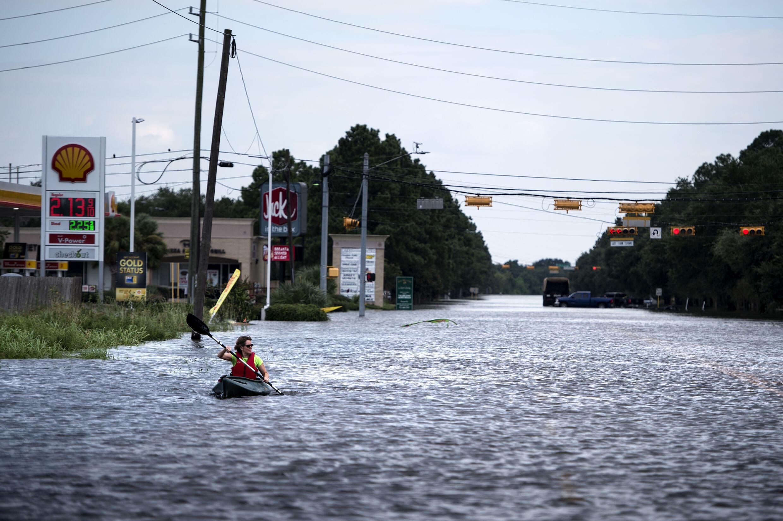 Una mujer rema en una piragua por una carretera anegada para llevar víveres a sus vecinos tras unas inundaciones provocadas por el huracán Harvey, el 30 de agosto de 2017 en Houston, al sur de EEUU