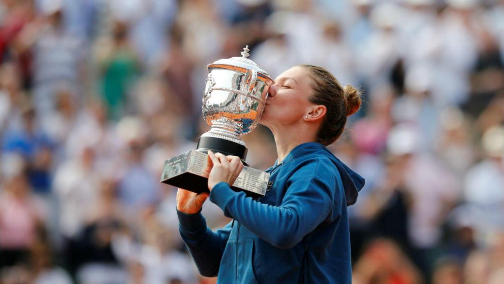 La tenista Simona Halep de Rumania, celebra su victoria en el Roland Garros besando el trofeo tras ganar la final contra Sloane Stephens en París. 9 de junio 2018.