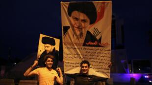 Los partidarios iraquíes de la lista Sairun celebran con retratos del clérigo chiíta Moqtada al-Sadr, después de que se anunciaran los resultados de las elecciones parlamentarias en Bagdad, Iraq, el 14 de mayo de 2018.