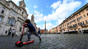 """طفل على دراجة """"سكوتر"""" في روما بتاريخ 29 نيسان/أبريل 2020"""
