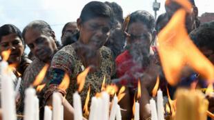Un devoto cristiano de Sri Lanka enciende velas fuera de la iglesia de San Antonio en Colombo el 21 de mayo de 2019, un mes después de una serie de explosiones mortales el domingo de Pascua.