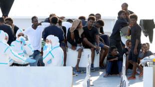 """Migrantes eritreos en el barco militar italiano """"Diciotti"""" atracado en el puerto de Catania en el sur de Sicilia a la espera de recibir la autorización del gobierno italiano para desembarcar.  Catania, Italia. Agosto 22,  2018"""