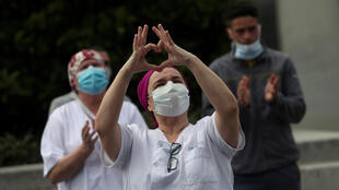 A nurse from La Paz hospital in Madrid, Spain makes a heart sign after observing a minute of silence in memory of the hospital chief who died from Covid-19, on 19 April, 2020.