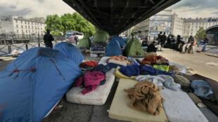"""مخيم أقامه مهاجرون تحت جسر"""" لاشابيل"""" في باريس"""