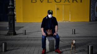 Un homme portant un masque est assis sur un poteau avec son chien en laisse, place Vendôme à Paris, le 21 avril 2020.