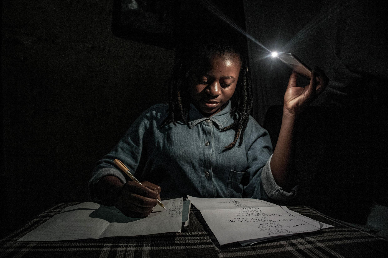 L'école en période de confinement. Marie, 13 ans, étudie chez elle à la lumière de son téléphone portable pendant une énième coupure de courant à Goma, dans l'est de la RD Congo, durant le printemps 2020.