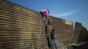 مهاجرون يتسلّقون سياجا في تيخوانا عند الحدود الأمريكية المكسيكية في 25 تشرين الثاني/نوفمبر 2018