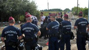 Face à des migrants, des policiers hrongrois bloquent un point de passage à la frontière avec la Serbie, le 14 septembre 2015.