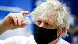 ILE PHOTO: Britain's Prime Minister Boris Johnson holds a vial of an Oxford-AstraZeneca COVID-19 vaccine, during his visit at a vaccination centre at Cwmbran Stadium in Cwmbran, south Wales, Britain February 17, 2021.