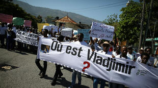 La gente lleva una pancarta durante la marcha para exigir información sobre el fotoperiodista desaparecido, Vladjimir Legagneur, en Port-au-Prince, Haití, el 28 de marzo de 2018.