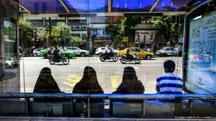 Women sit as they wait for a bus at a stop along a street in the Iranian capital Tehran